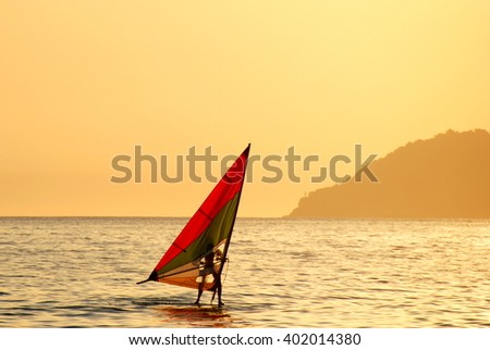 Windsurfer silhouette at sunset on a summer day - stock photo