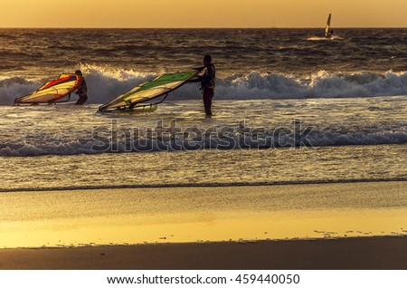 Windsurfer speeding fast against the sunset in soft focus. Summer sports. Freedom - stock photo