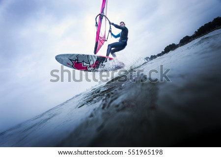 Windsurfer stunting on waves