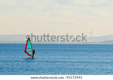 Windsurfer with wind turbine in the background