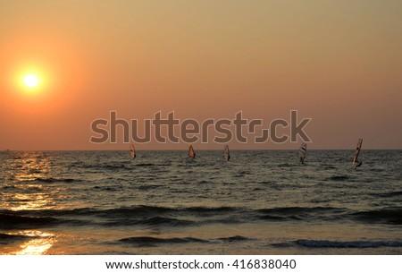 Windsurfers at sunset - stock photo