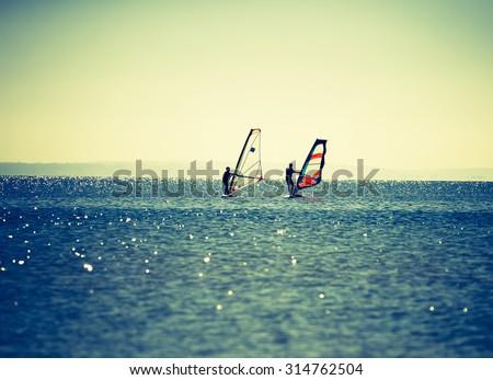 Windsurfers swimming in sea. Summertime photo with windsurfers swimming on water surface - stock photo