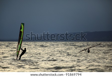 Windsurfing at overcasted sky Lake Balaton - stock photo