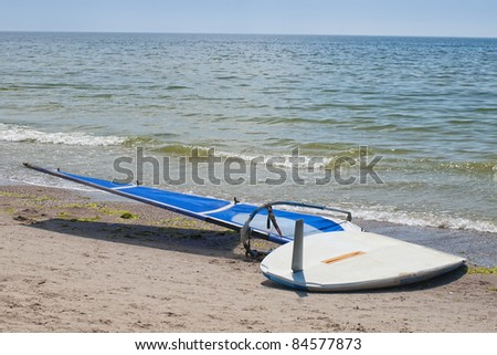 Windsurfing board with sail lying on the sand and windless sea - stock photo
