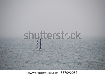 Windsurfing. Lifestyle and sport concept. Fun and leisure activity. Windsurfer in the sea, man on windsurf conquering the waves, enjoying extreme sport, active lifestyle, happy vacation.