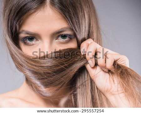 Windswept beauty. Beautiful young woman covering her face by hair while standing against gray background.