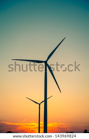 Windturbine farm at the sunset - stock photo