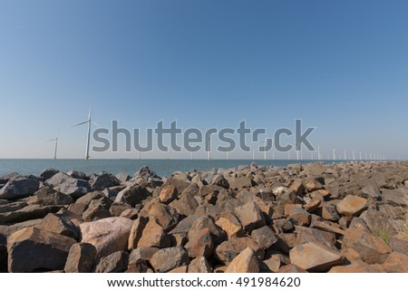 Windturbines  in the water producing alternative energy and a pile of rocks