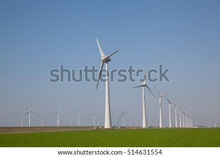 Windturbines producing alternative energy with a clear blue sky.