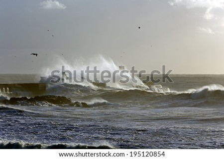 Windy waves over beacon of Douro river harbor at sunset before storm - stock photo