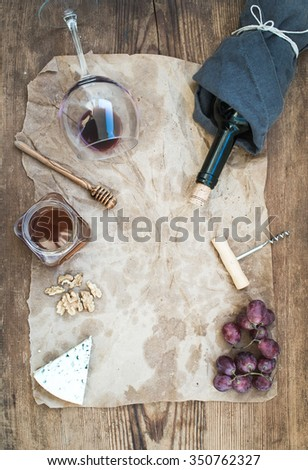 Wine and appetizer set with copy space in center. Glass of red wine, bottle, corkscrew, blue cheese, grapes, honey and walnuts on oily craft paper over rustic wooden table, top view