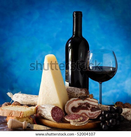 Wine and cheese and salami on a blue colored background