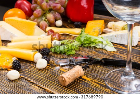 Wine and Cheese Concept Image - Close Up of Empty Wine Glass, Opener and Cork on Rustic Wooden Table Surrounded by Variety of Cheeses and Fruit - stock photo