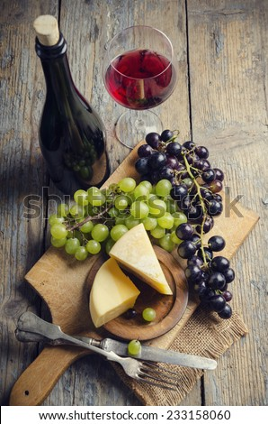 Wine and cheese on rustic wooden table - stock photo