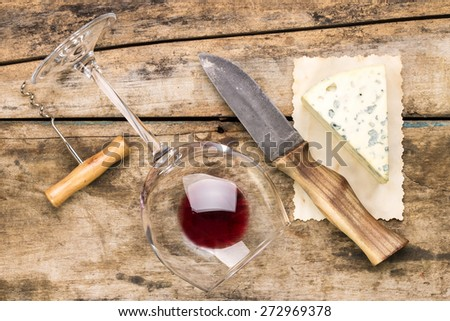 Wine and cheese set background. Blue cheese with knife, wineglass and corkscrew on wood background - stock photo