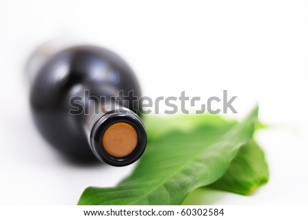 wine and copyspace on white with green leaves - stock photo