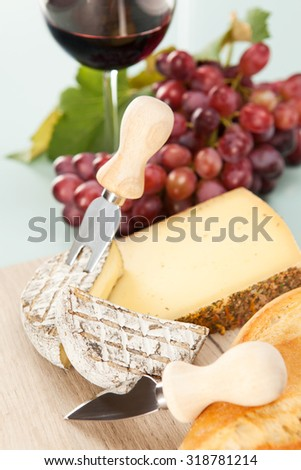 Wine and grapes with cheese plate and baguette