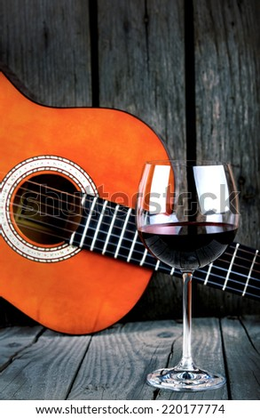 Wine and Guitar on a wooden table vintage retro photo - stock photo