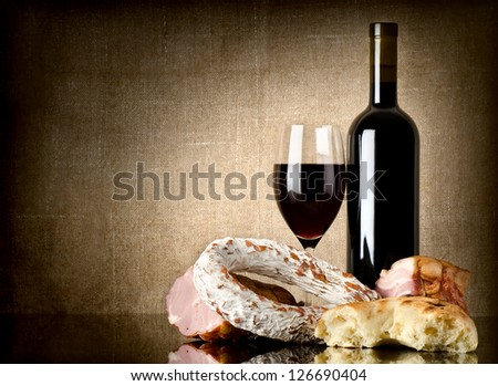 Wine and sausage, bread on an old canvas - stock photo