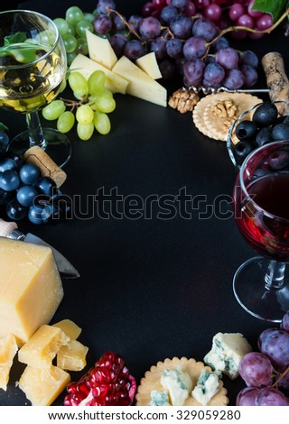 Wine and snacks arranged in the form of a border on a black background - stock photo