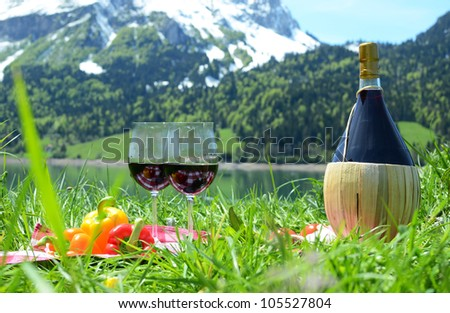 Wine and vegetables served at a picnic on Alpine meadow. Switzerland - stock photo
