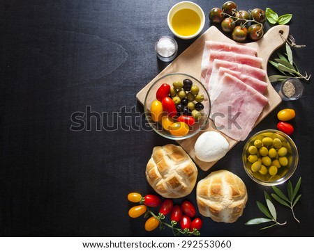 Wine appetizer set. Antipasti Platter of baked ham, red and yellow Grape Tomatoes, black zebra cherry tomato, black and green olives, the leaves of the olive tree, salt and pepper, bread turtle. - stock photo