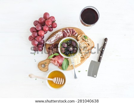 Wine appetizer set. Glass of red wine, grapes, honey, parmesan cheese, meat variety, bread slices, pecan nuts, honey, olives and basil on rustic wooden board over white wood backdrop, top view - stock photo