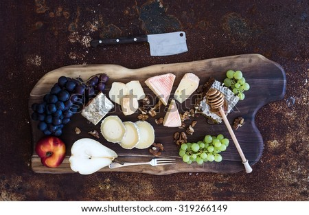 Wine appetizers set: French cheese selection, honeycomb, grapes, peach and walnuts on rustic wooden board over dark grunge metal background. Top view,