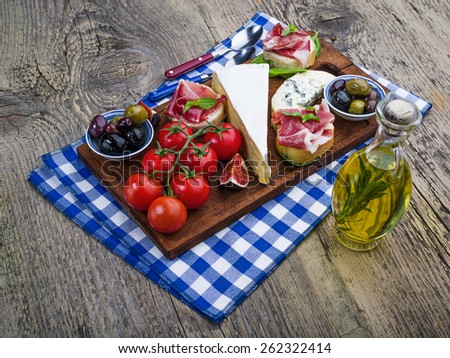 Wine appetizers set: meat and cheese selection, olives, walnuts and olives on a dark rustic wooden background - stock photo