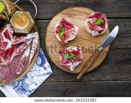 Wine appetizers set: meat and cheese selection, walnuts and olives on a dark rustic wooden background