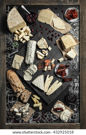 Wine appetizers set on the top view: cheese selection, bread sticks and prunes on the wood serving board background. - stock photo