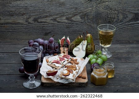 Wine appetizers set: Sandwiches with cheese and figs, grapes, pears and plum on a dark rustic wooden background - stock photo