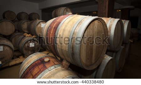 Wine barrels in cellar. Cavernous wine cellar with stacked oak barrels