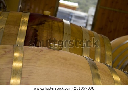Wine barrels stacked in cellar area of vinery - stock photo