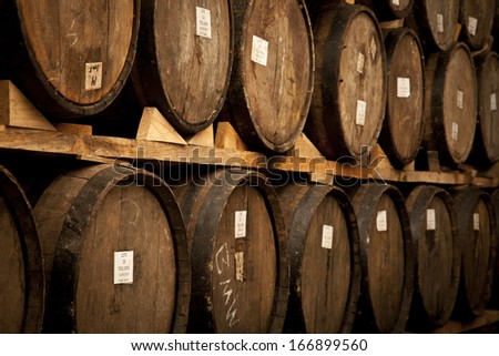 Wine barrels stacked in the old cellar of the winery. - stock photo