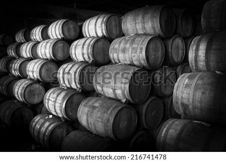 Wine barrels stacked in the old cellar of the winery. Black and white - stock photo