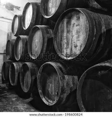 Wine barrels stacked in winery old, in black and white - stock photo