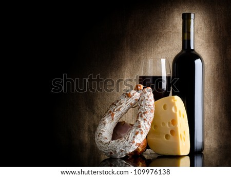 Wine bottle and cheesei on a background of old canvas
