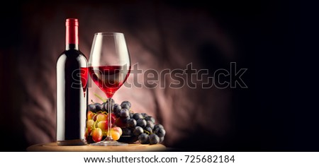 Wine. Bottle and glass of Red wine with ripe grapes still life. Red wine Over black background. Border art design.