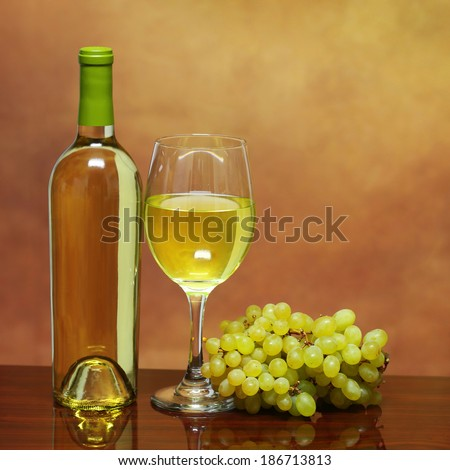 Wine Bottle and Glass of White Wine with Fresh Grapes over beige background. Chardonnay