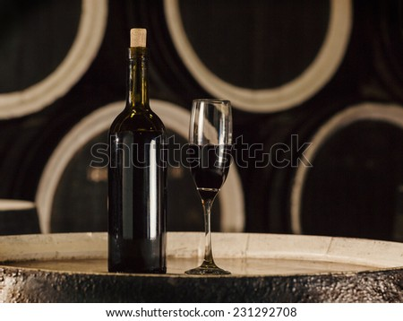 Wine bottle and glass wine glass on wooden barrel in the old cellar. - stock photo