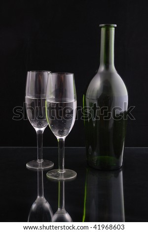 Wine bottle and pair of champagne flutes against a black background - stock photo