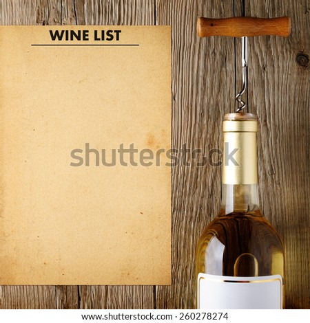 Wine bottle and wine list on wooden background - stock photo