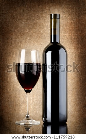 Wine bottle and wineglass on a old canvas - stock photo
