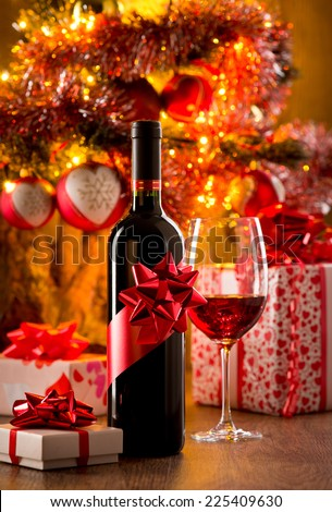 Wine bottle gift and wine glass filled with red wine, christmas gift boxes and tree on background. - stock photo