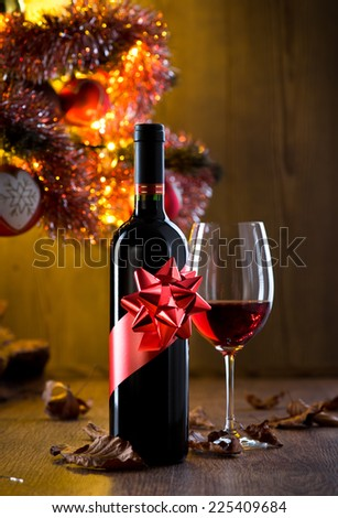Wine bottle gift and wine glass filled with red wine, christmas tree and dry leaves on background. - stock photo