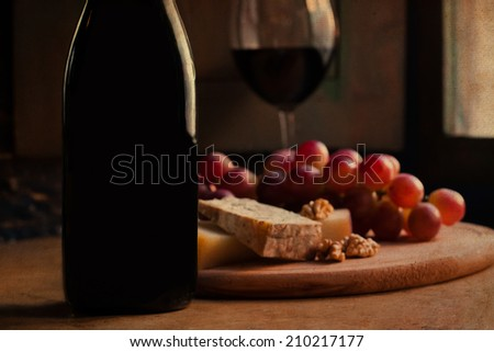 Wine bottle, glass and cheese plate. Very soft focus effect toned vintage paper.