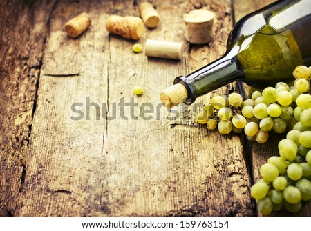 Wine bottle , grape and corks on wooden table / summer wine background - stock photo