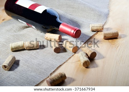Wine bottle lying on wooden table with burlap cloth and corks scattered around with copy space - stock photo