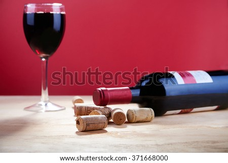 Wine bottle lying on wooden table with burlap cloth, glass and corks  with copy space - stock photo